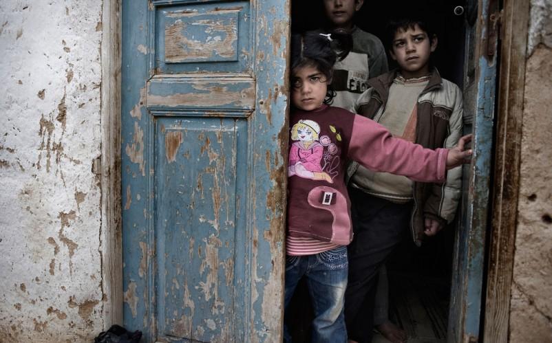 Syrian Children taking refuge in a door - Photo Courtesy UNUCEF