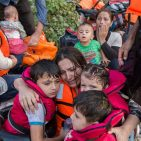 A Syrian mother cries with relief as she embraces her three young children after a rough sea crossing. Photo Credit:  UNHCR/Ivor Prickett