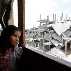 A Palestinian girl inside her family's partially destroyed home, looks at the destruction outside, in the Shejaiya neighbourhood of Gaza City. Photo: UNICEF