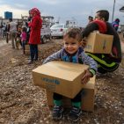 A three-year-old boy sits on a box of winter clothing that his family has received from a distribution at Kawergosk Syrian Refugee Camp in Erbil Governorate in the Kurdistan region of Iraq. Photo: UNICEF/Khuzaie